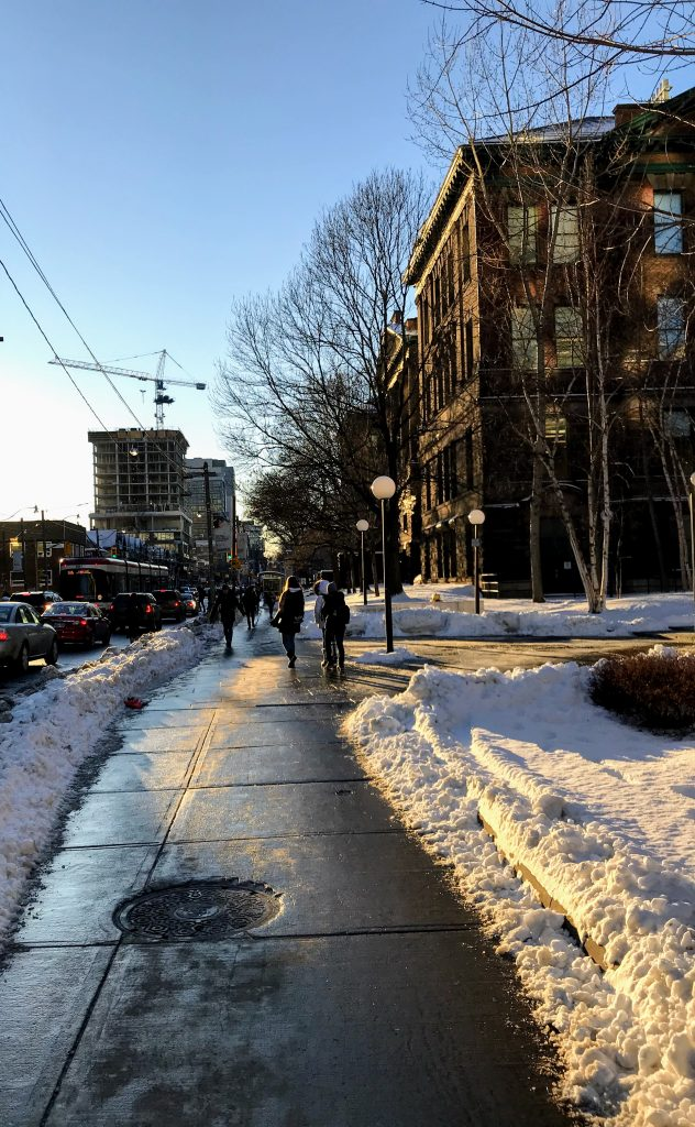 Picture of sidewalk on north side of College by Campus. There is snow on the ground and people in the background.