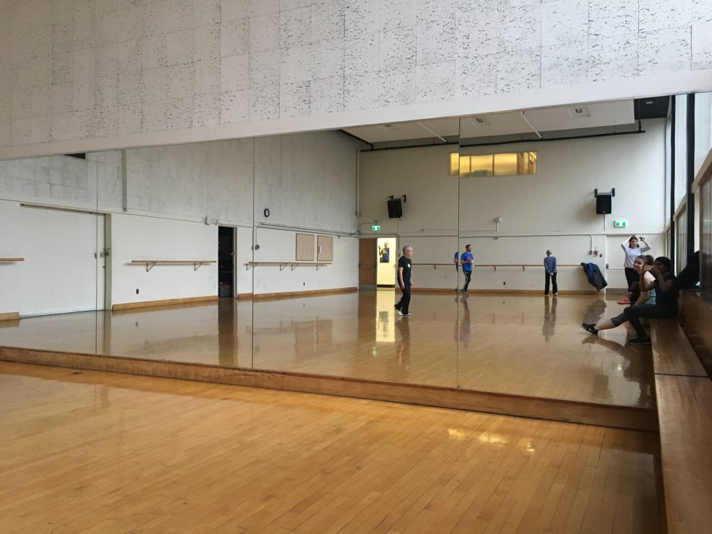 A large mirror fills an entire wall, which reflects a wood panelled room. A few people are milling around.