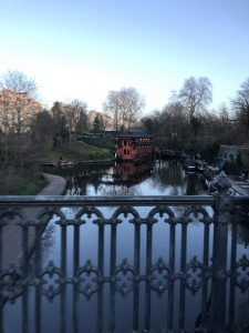 View of the Camden canal from a bridge. There's trees on both sides and there is a boat in the canal.