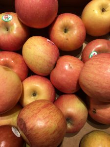 Light pink apples stacked on top of each other.