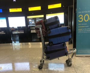 Three suitcases piled on top of each other on an airport cart.