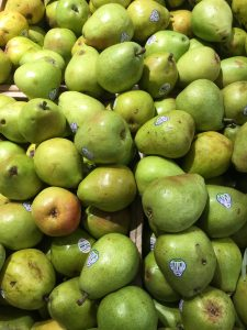A trough full of green pears with price stickers on them.