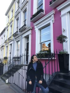Francesca looking up to a house with a pink facade.
