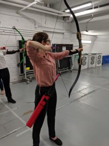 Woman in pink shirt holding a bow and arrow