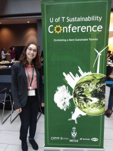 "Girl standing next to a green upright banner that says ""U of T Sustainability Conference"""