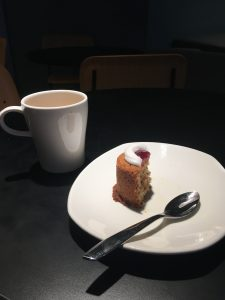 A half-eaten Runeberg Torte sits on a plate next to a cup of coffee