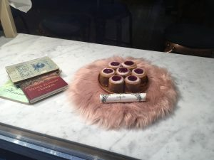 A cluster of Runeberg Torte cakes rest on top of a pink pillow in a window display.