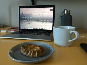 A Karelian Tart sits on a plate next to a mug, with a laptop in the background.