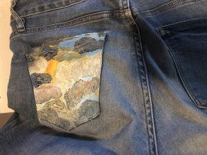 The back pocket of a pair of jeans is painted with clouds.