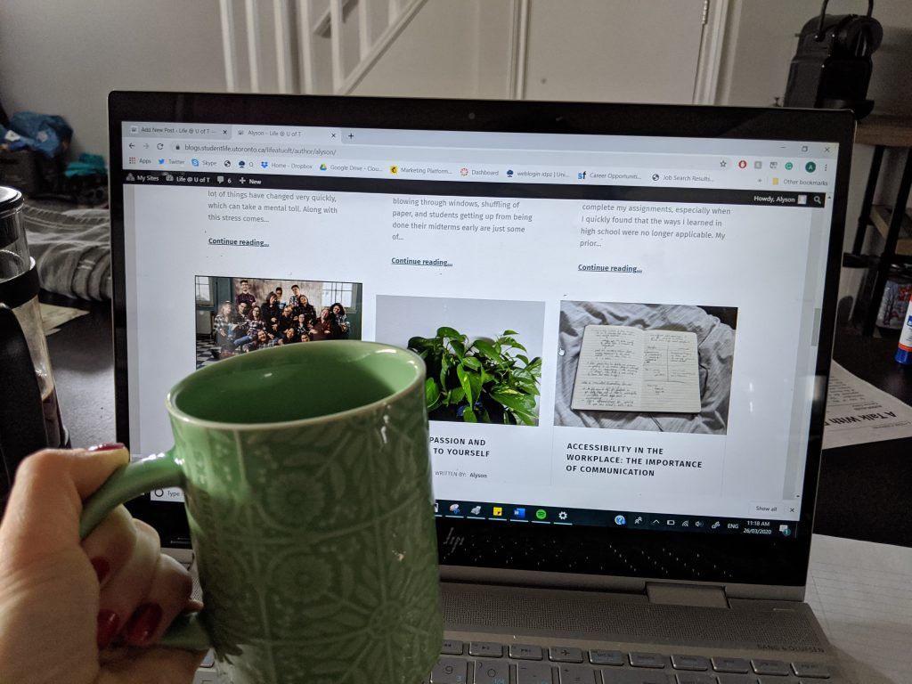 Green coffee cup held in front of a laptop open to various blog posts