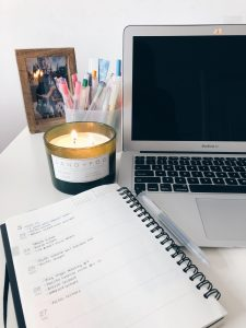 Picture of my laptop, candle, agenda