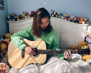 Picture of me on my bed, holding a guitar