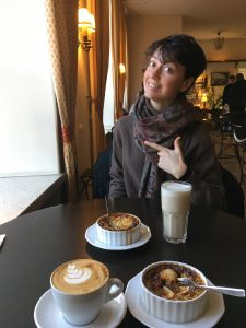 A girl sits across a table, which is set with coffee, tea and quiche