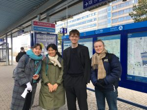 Three women and one man stand together on a train platform, smiling for the camera.