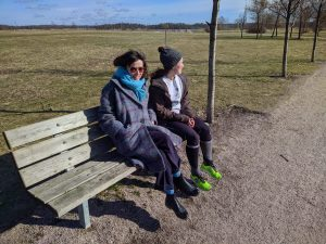 Two girls sit on a park bench in front of a green field. One faces the camera, one looks into the distance.