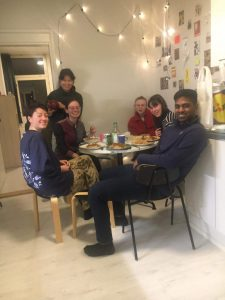 Six people seated around a kitchen table full of food, smiling for the camera.