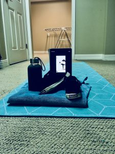 A blue yoga mat set up with a blue towel, black running shoes, grey water bottle, and iPad, which displays a yoga video.