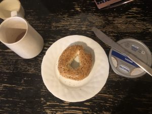 A coffee mug and a bagel with cream cheese.