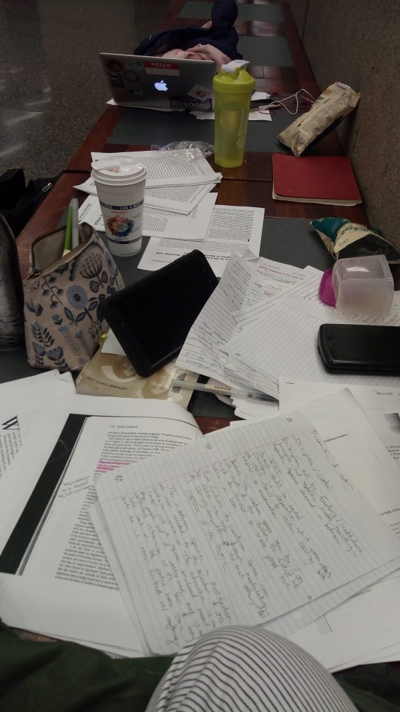 papers messily covering table with pencil case and laptop