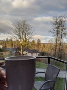 Mug being held with landscape of trees in the background