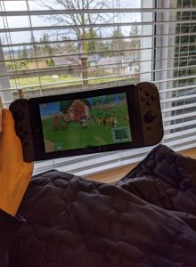 Hand holding a Nintendo Switch in front of a window