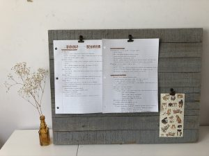 a wall clip frame with notes clipped on, stickers, and flowers on the side