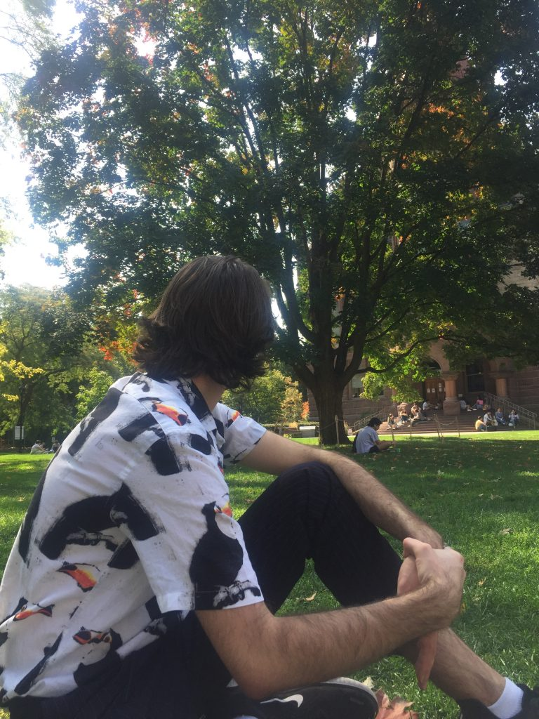A picture of a person sitting in the Vic College quad