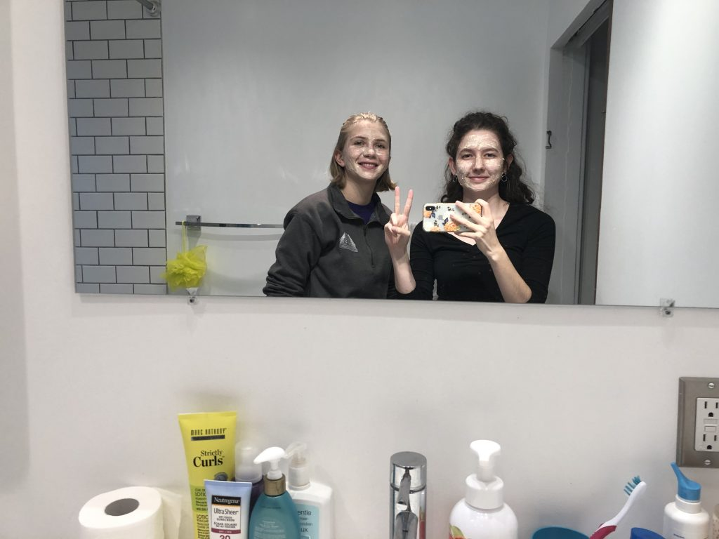 Friend and I wearing face masks, posing in the mirror.