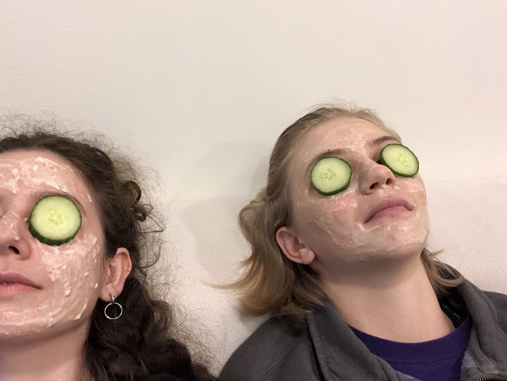 Friend and I wearing face masks with cucumber over our eyes.