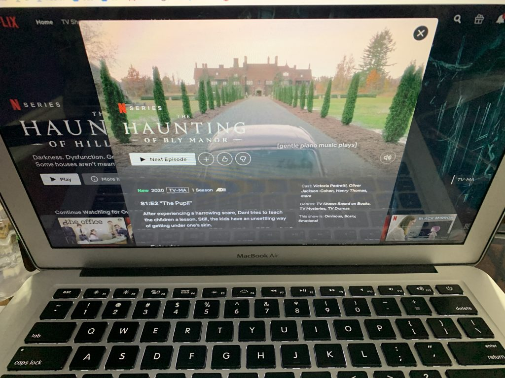 MacBook Air with the screen showing the introduction of the Netflix show called 'the Haunting of Bly Manor'