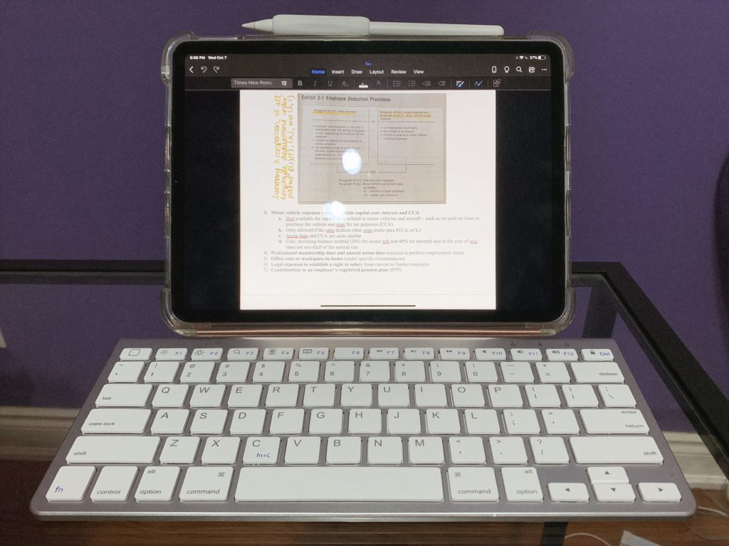 iPad Pro opened on a word document with apple pencil attached and paired with a white bluetooth keyboard