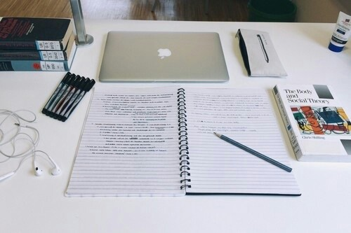 An image displaying a study layout of books, writing utensils and a laptop.