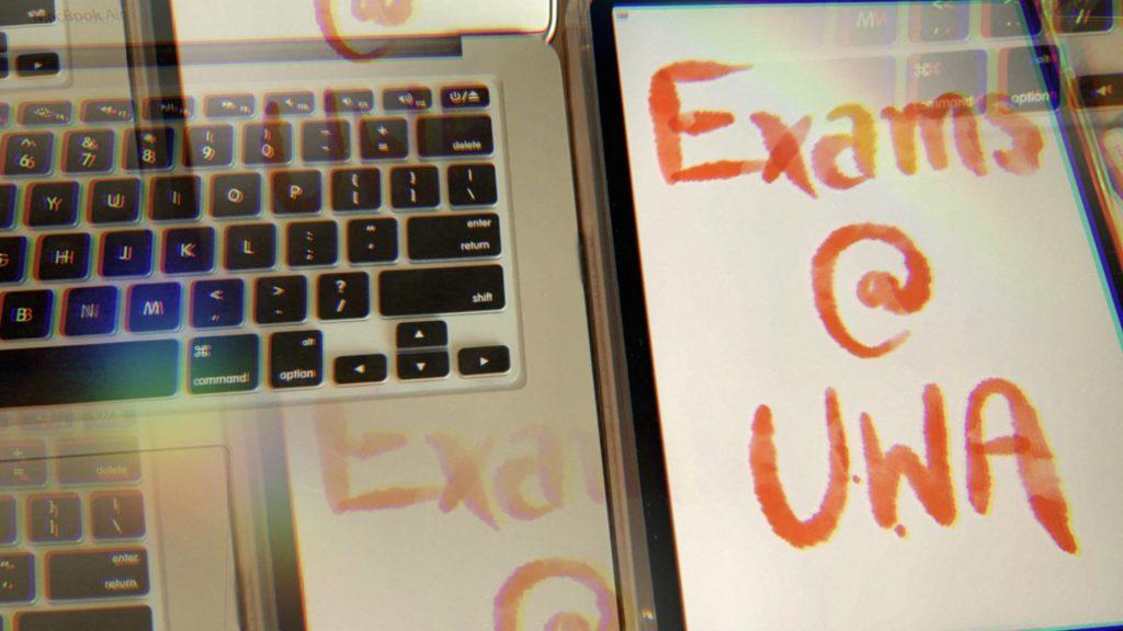 "Laptop keyboard and iPad Screen reading ""Exams @ UWA"""