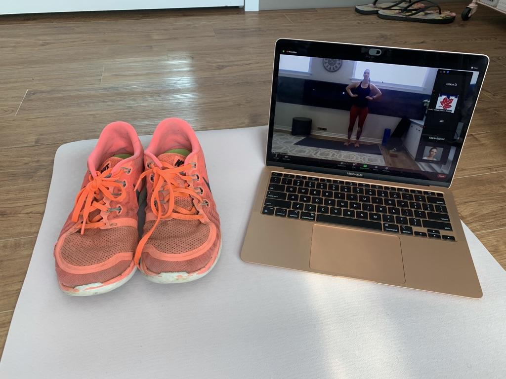 shoes on a yoga mat besides laptop