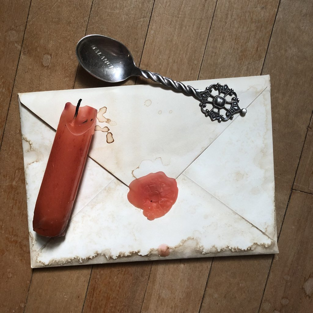 Envelope with wax seal and teaspoon.