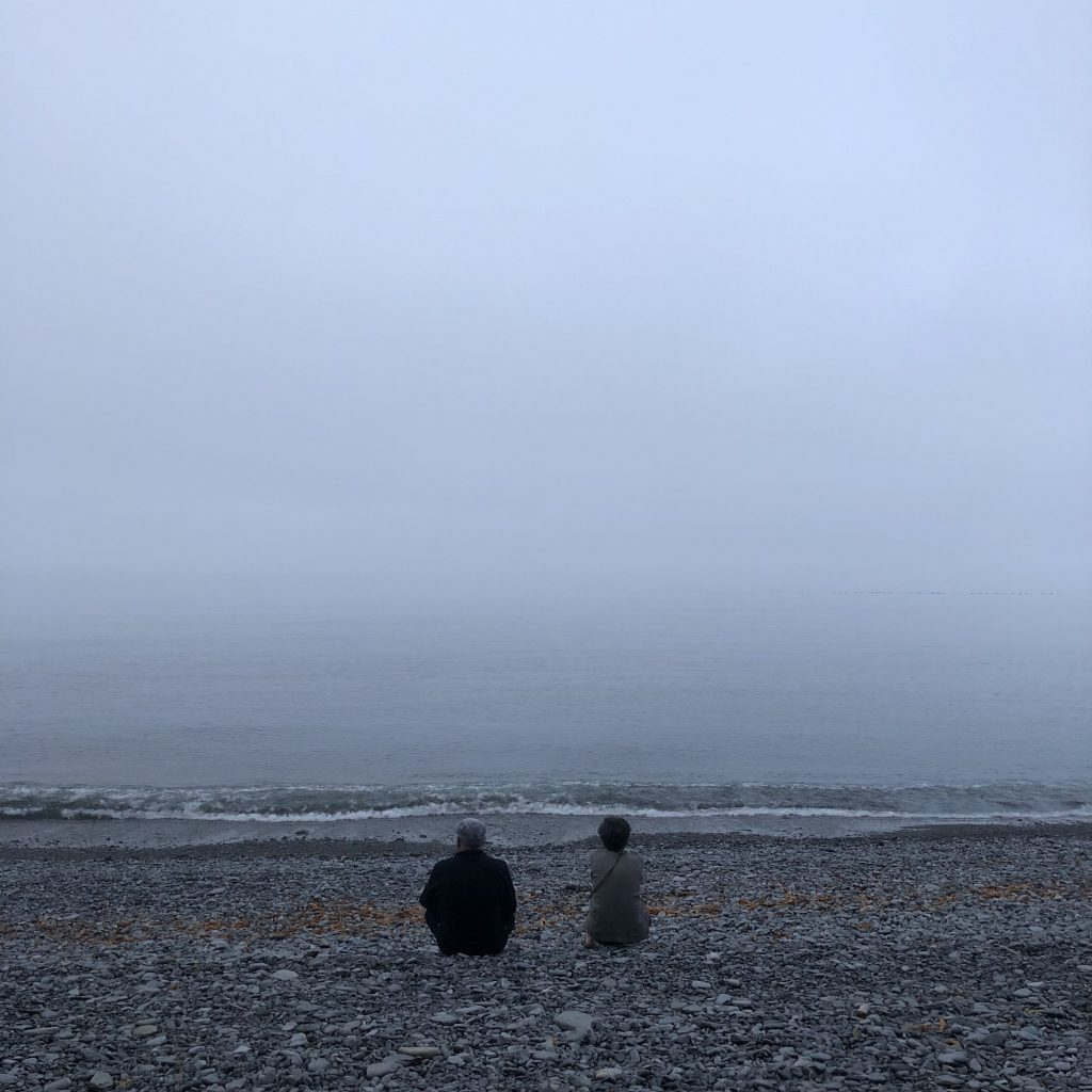 Two people, with their backs turned, sitting on a foggy beach.