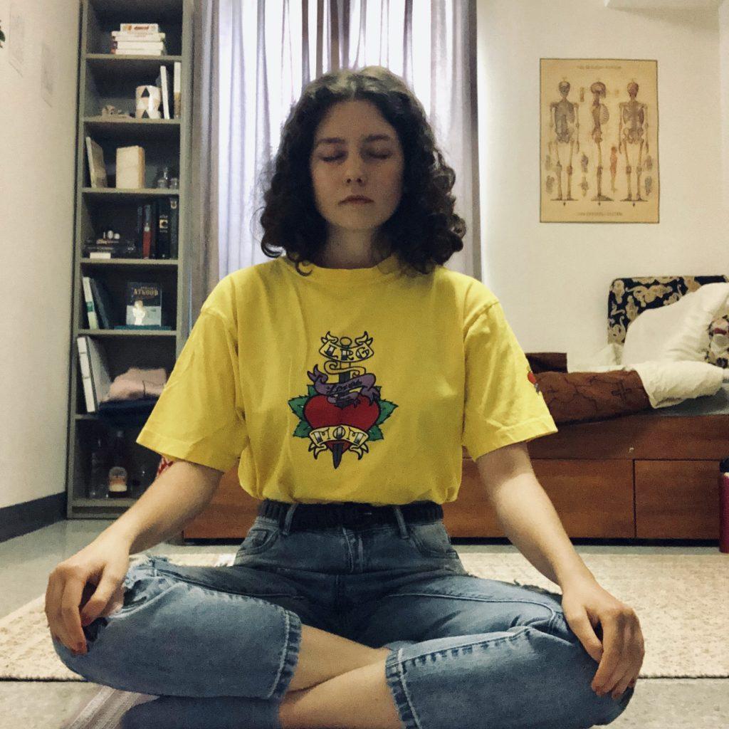 Olive, sitting cross-legged on a yoga matt, eyes closed, meditating.