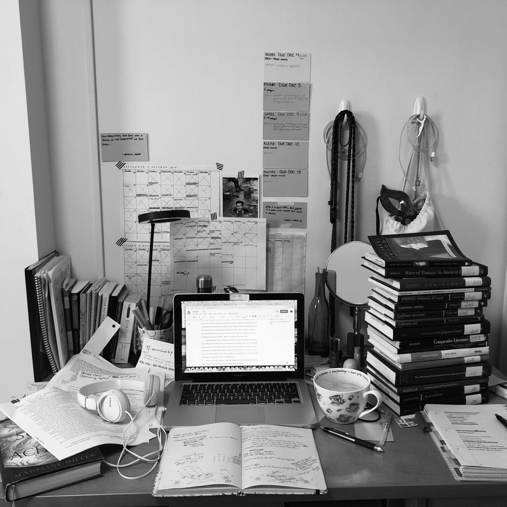 Messy desk, black and white photo, stacked with library books.