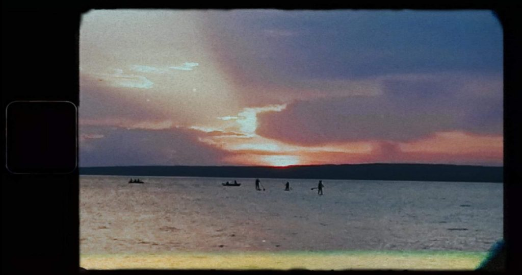 Grainy sunset photo of lake and fishermen (mostly blue and purple).