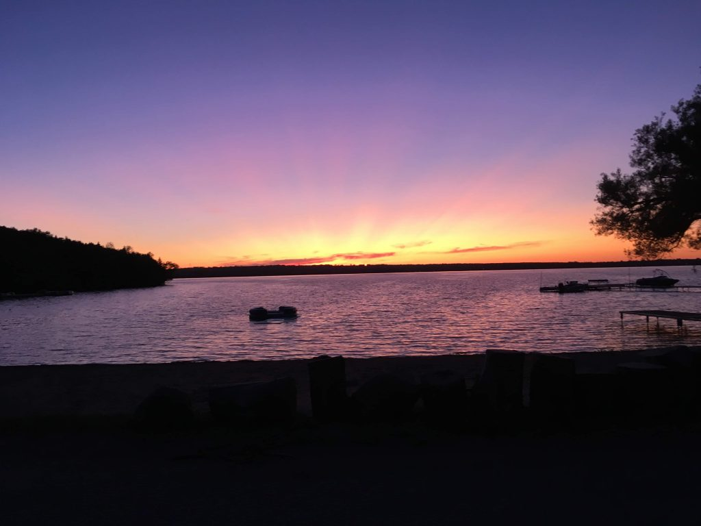 Sunrise photo over lake (mostly purple and pink).