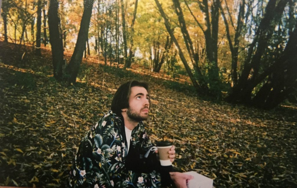 A picture of a person sitting on the ground in a wooded park