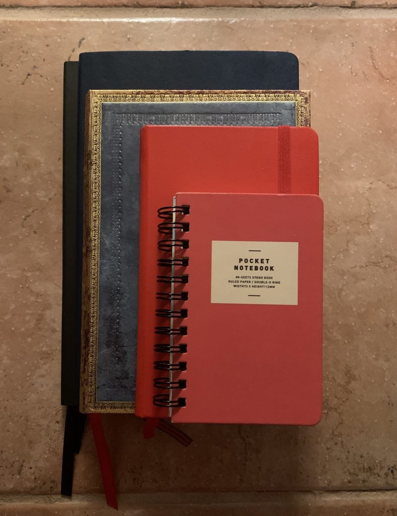 A photo of five journals stacked on top of each other