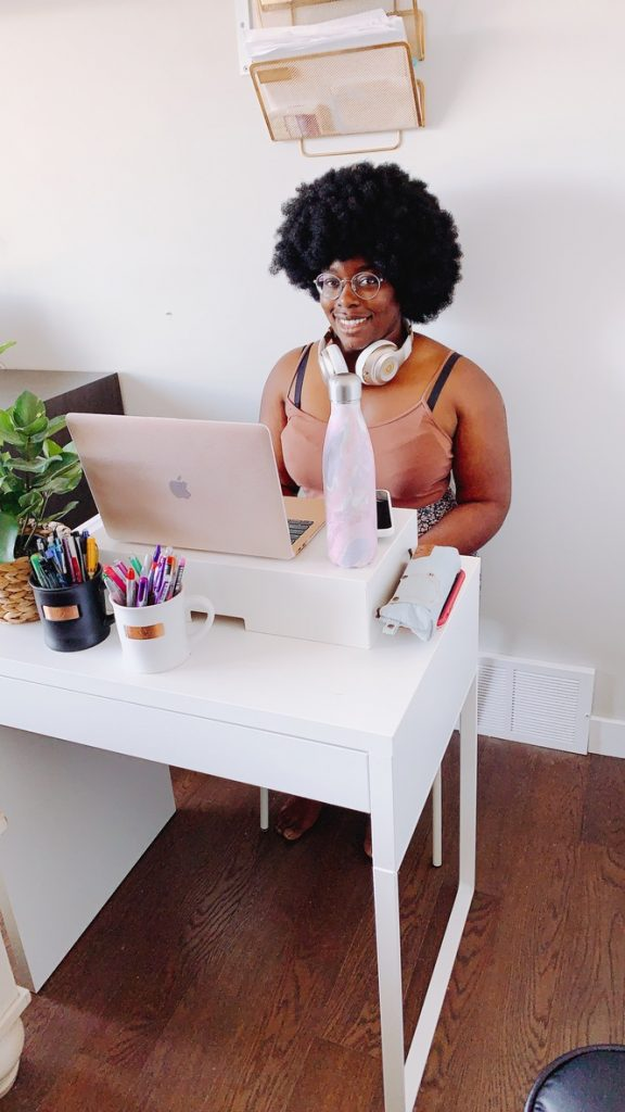 girl with afro wearing headphones around neck sitting at a white desk with a pink macbook air laptop