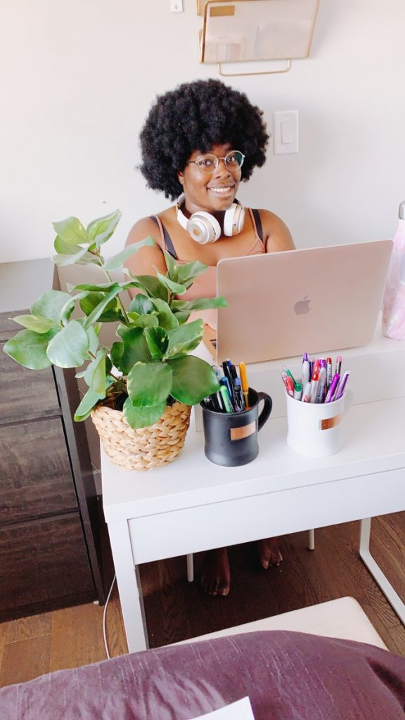 girl smiling while working on a pink macbook air laptop and sitting in front of a plant and a white mug of colored pens