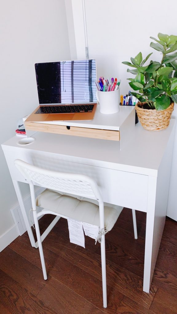 white desk and chair set with open macbook air and plant in a beige basket