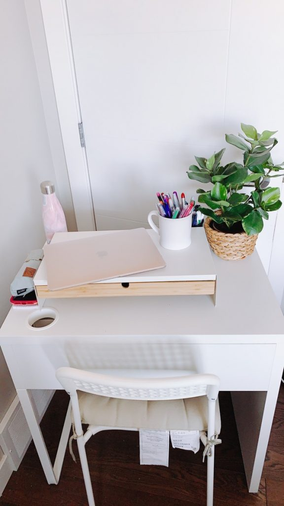 white desk and chair set with white mug filled with coloured pens and an open macbook air and plant in a basket
