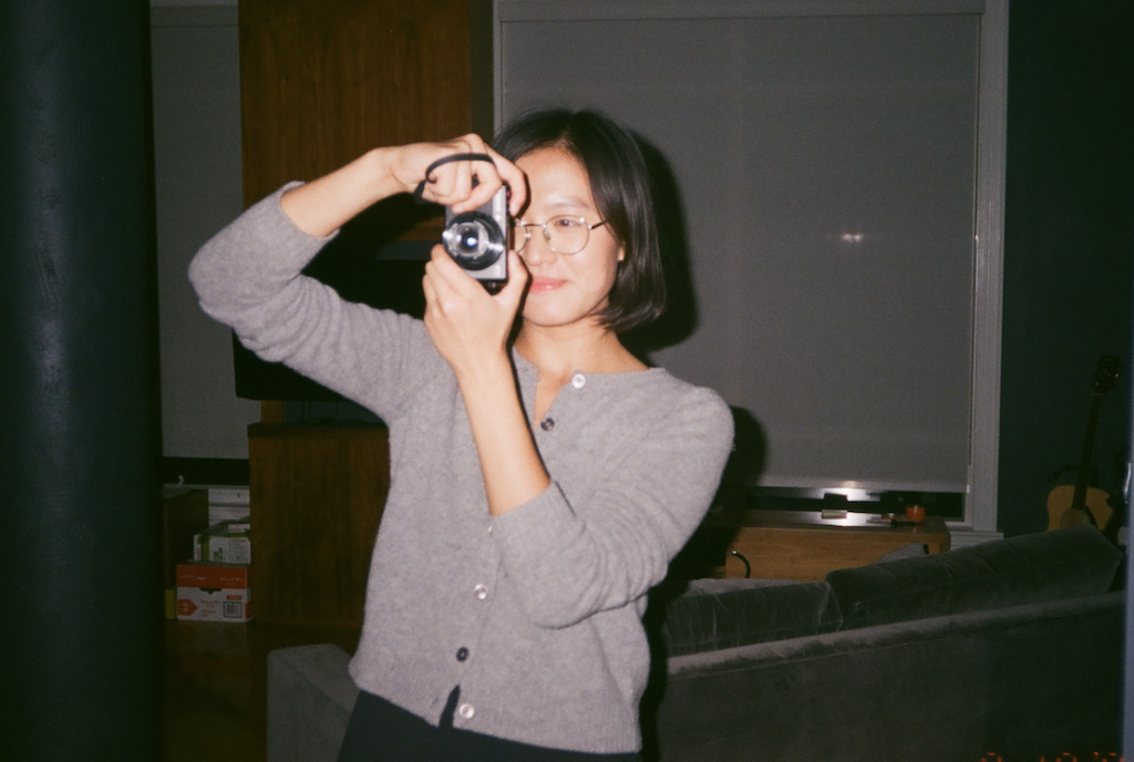 the author raises a camera to her eye in a living room