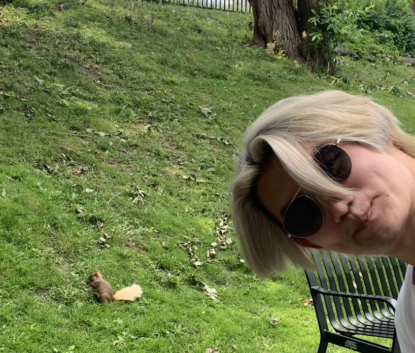 a blonde student in the foreground with a blonde squirrel in the background