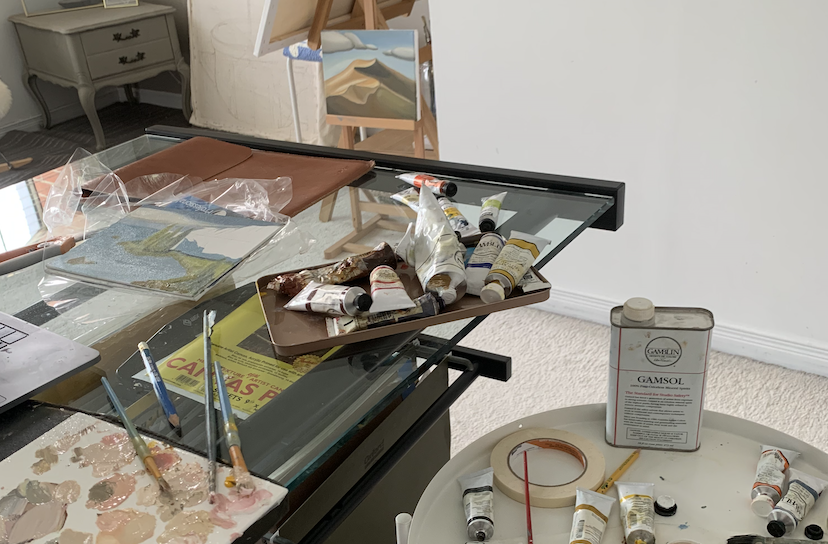 two oil painting palettes on two tables, one of which also has paint brushes, tape, and paint thinner
