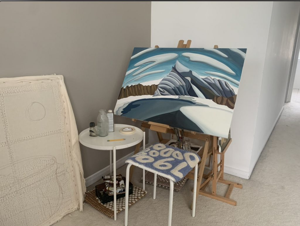 An unfinished painting of mountains in the winter sits on an easel